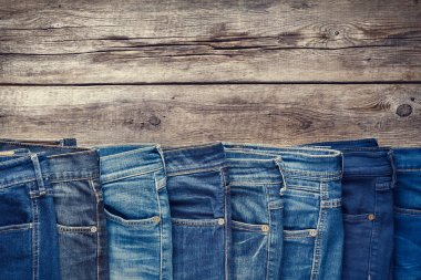 Fashion different jeans on wooden background.