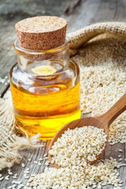 bottle of oil sesame seeds in sack on old wooden table