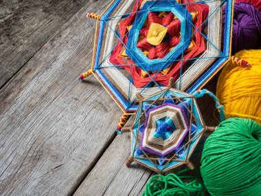 Knitted mandala and yarn on rustic table