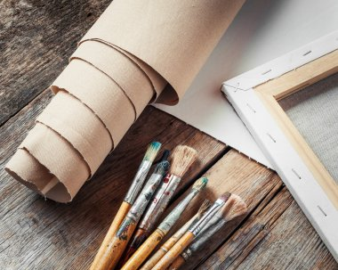 Artist canvas in roll, canvas stretcher and paintbrushes on old table stock vector