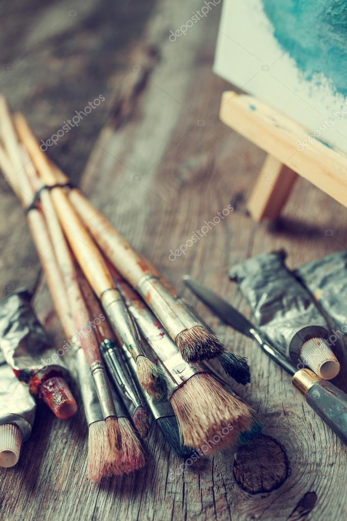 Artistic paintbrushes, tubes of oil paint, palette knife and eas