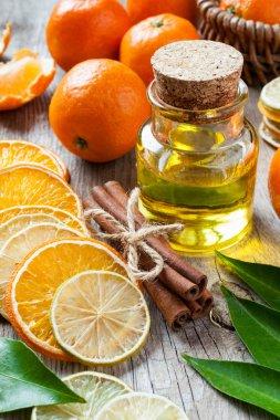 Bottle of essential citrus oil, dried orange and lemon slices, c