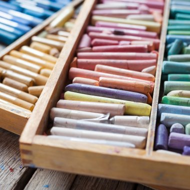 Set of multicolored pastel crayons in open wooden artist box on