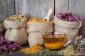 Léčivé byliny v zkřížili tašky a šálek zdravé čaje, bylinné medici