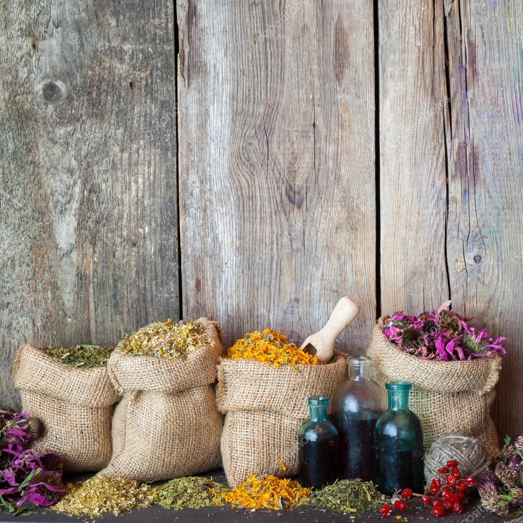 Healing herbs in hessian bags and blue bottles with tincture on