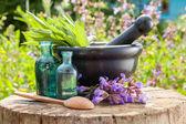 Fekete habarcs zsálya gyógynövényekkel, illóolaj, üvegek