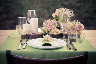Retro stylized photo of wedding table setting in rustic style.
