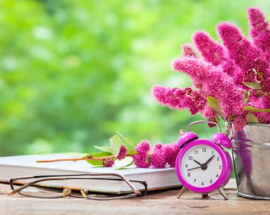 Vintage still life: flowers in bucket, pink alarm clock and buck