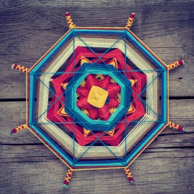 Knitted tibetan mandala from threads on old wooden background