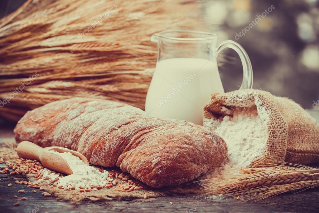 Fresh bread, jug of milk, flour and sheaf of wheat on wooden tab