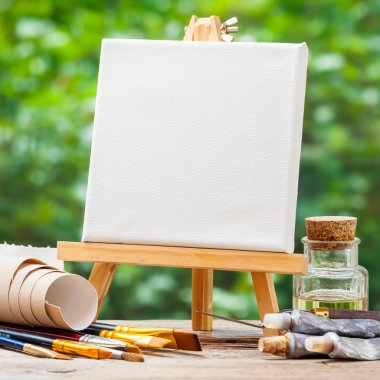 A blank canvas on easel, artistic paintbrushes, tubes of oil pai