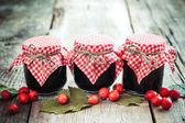 Fotografie Three jars of jam and hawthorn berries on rustic table