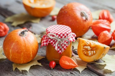 Pumpkin jam, puree or sauce and pumpkins on wooden table.