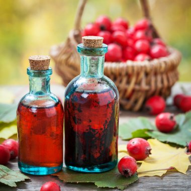Bottles of hawthorn berries tincture and red thorn apples in b