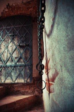 Fragment of medieval dungeon prison. Focus on ancient door.