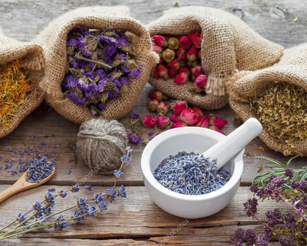 Healing herbs in hessian bags and mortar with dry lavender