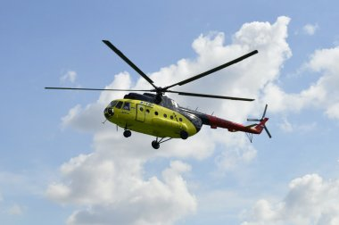The yellow MI-8 helicopter flies against clouds.