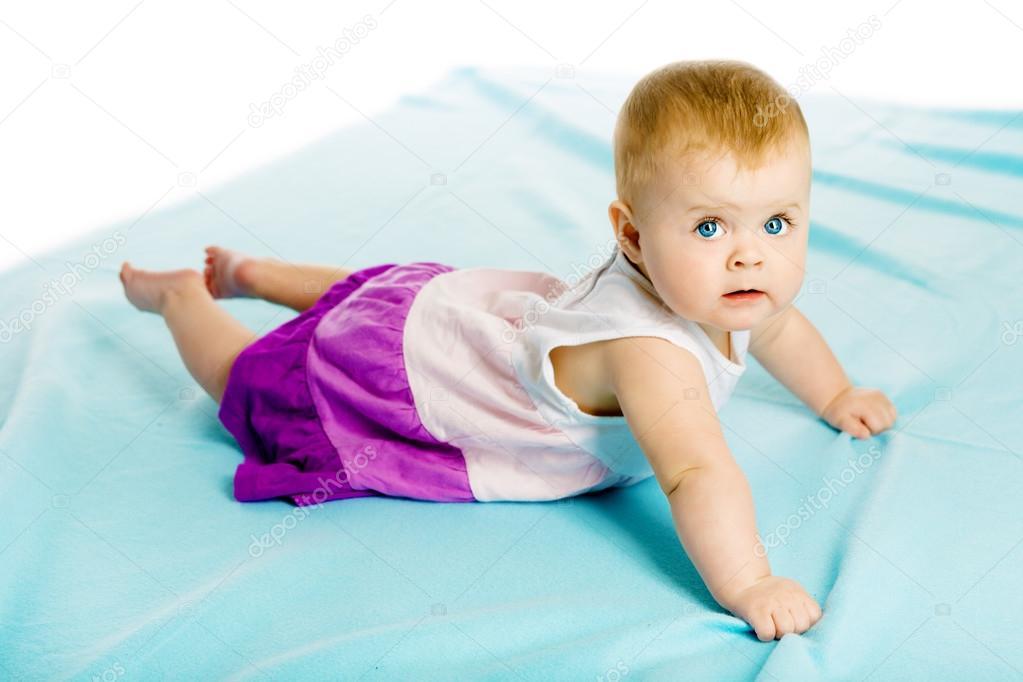Petite Fille En Robe Se Glisse Sur Le Couvre-lit Bleu