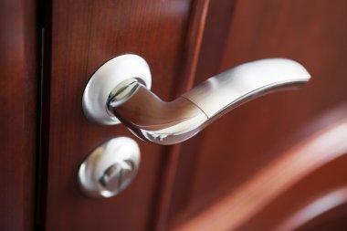 The metal door handle on a brown door