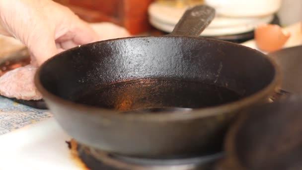 Smažené na pánvi v popředí. Babiččina ruce takže mleté steak (kotlety, masové kuličky) sekaná