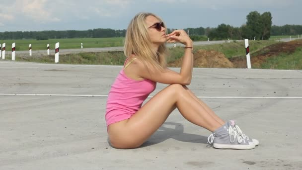 Young beautiful sexy booty dancer posing on blue sky background. Summer close up of hot blonde girl wearing mini trousers,swag black glasses, blue sneakers.