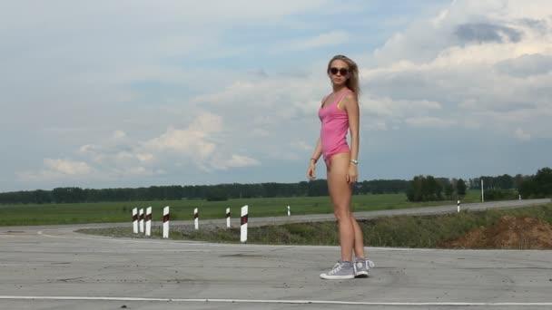 Ballerino di bottino sexy bella giovane in posa su sfondo blu cielo. Estate nelle vicinanze fino di calda ragazza bionda che indossa pantaloni mini, swag nero occhiali, scarpe da tennis blu