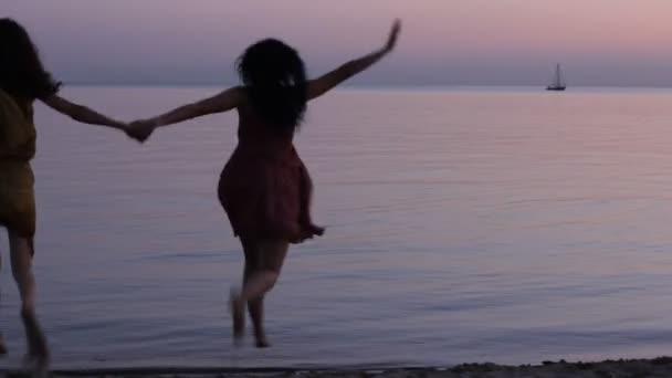 Sziluettjét boldog asszony tánc-naplemente a tengeren.