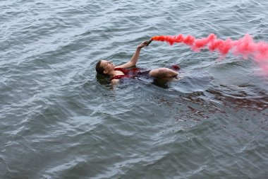 Young beautiful drowned woman with smoke grenade in red dress floating in the water after ship crush.