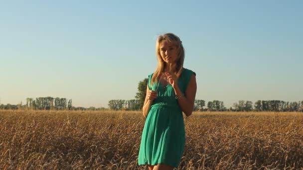 Krásná dívka pózuje na prosluněné obilné pole. Koncept svobody. Šťastná žena baví venku v pšeničné pole na východ nebo západ slunce.