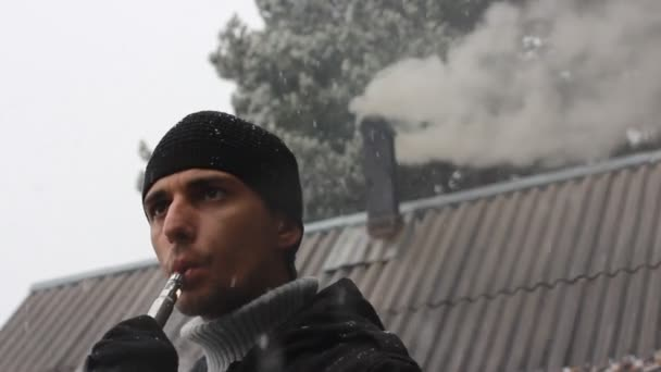 Zimní scenérie. Muž kouření elektronické cigarety. Střechy s kouře z komína. Padající sníh