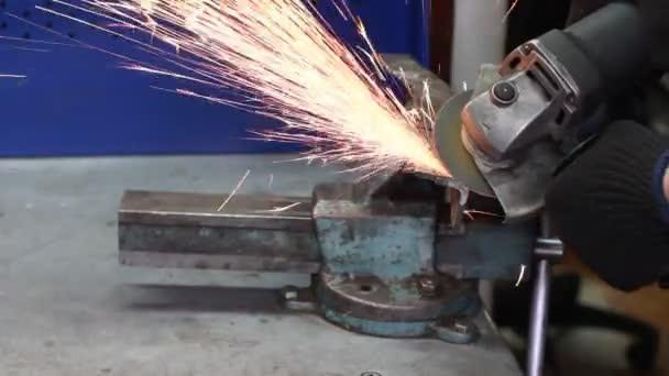 Pracovník pomocí průmyslové drtiče. Nástroj na kovových broušení kovových výrobků.