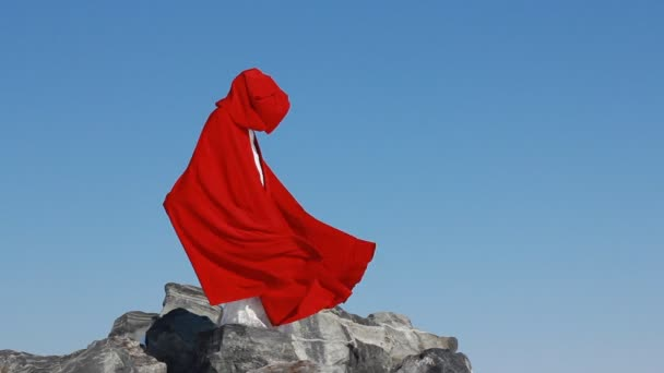 Bride stands on cliff with a flowing red raincoat on the wind against the blue sky and winter background.