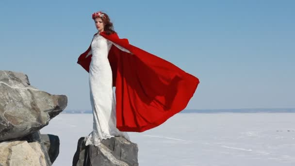 Nevěsta stojí na útesu s teče červená pláštěnka na vítr proti modré obloze a zimní pozadí