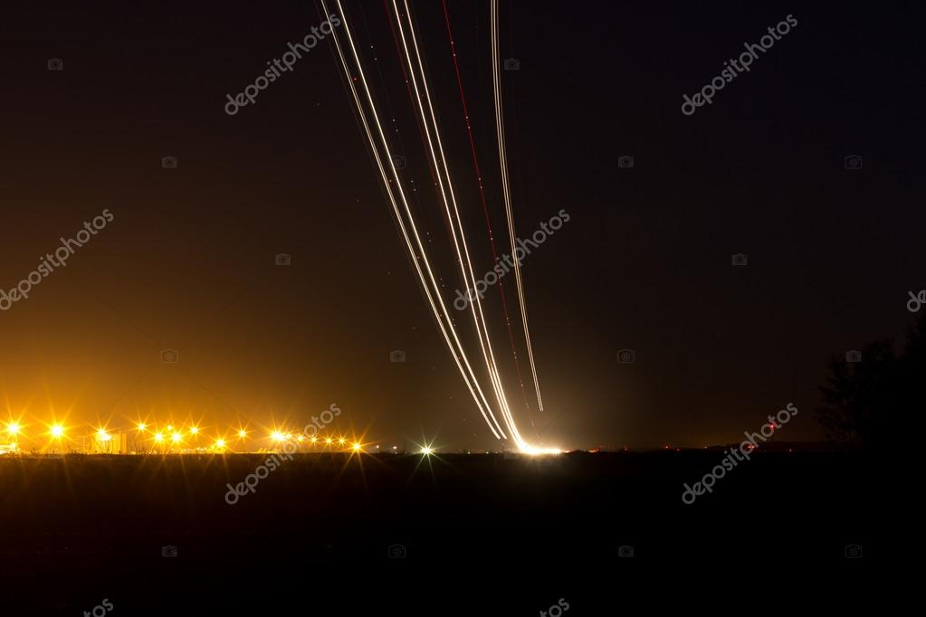Passenger planes take off from runways against beautiful night sky with moon. Long exposure. Motion blur, and light trace