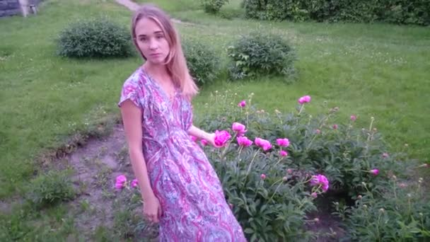 Young beautiful woman in a sundress posing with peonies in a garden. Fashion model girl touch of flowers outdoors in summer background.