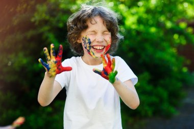 Child laughs, his face and hands in the paint