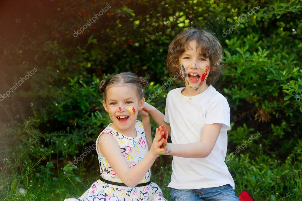 Kids soiled with paint, smiling and look into the camera.