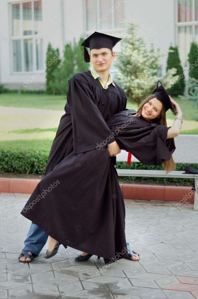 a857b4a8 Młody mężczyzna i kobieta szczęśliwie taniec ubrania absolwentów ...