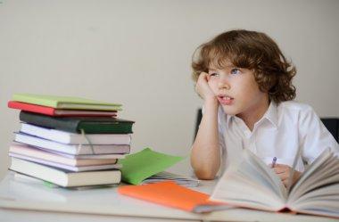 Dreamy schoolboy does his homework