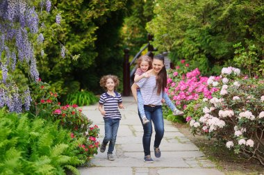 Mother with two children on a walk in Japanese garden