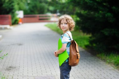 Schoolboy goes to school with a satchel behind shoulders.