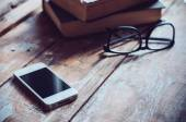 knihy, smartphone a brýle