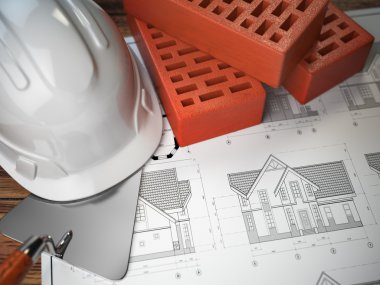 Hard hat, trowel and bricks on the drawings with construction pl