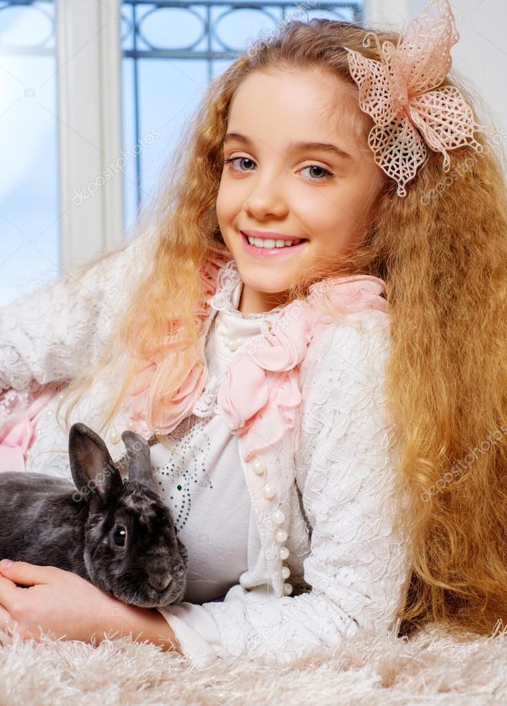 Hermosa ni a sentada en la alfombra y jugando con conejito lindo fotos de stock nejron - Alfombra nina ...