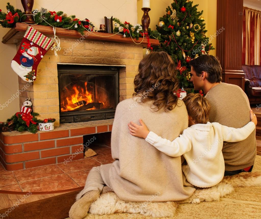 Famille près de la cheminée de noël décorée maison image de nejron