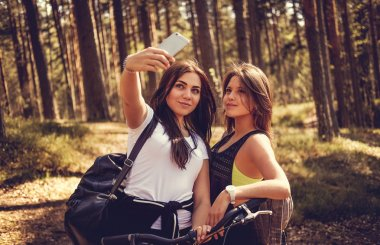 Two female with bicycles making selfie