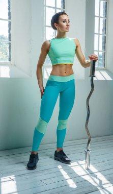 Female in sportswear with barbell.