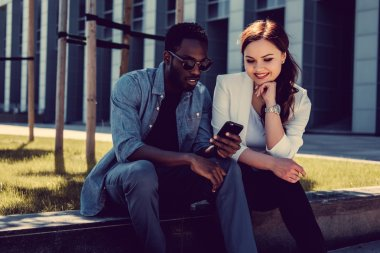 male and caucasian female with smartphone