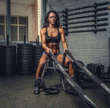 Female exercising with battle rope