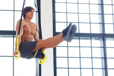Male exercising with fitness trx straps